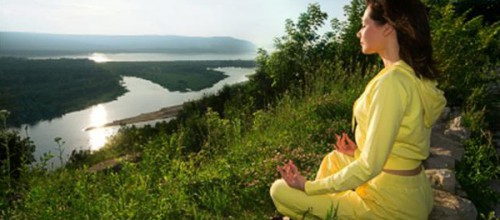 young beautiful woman meditate on mountain with peaceful view